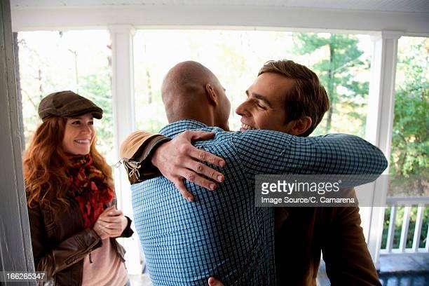 Men hugging at front door