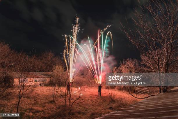 Men Igniting Fireworks On Field At Night