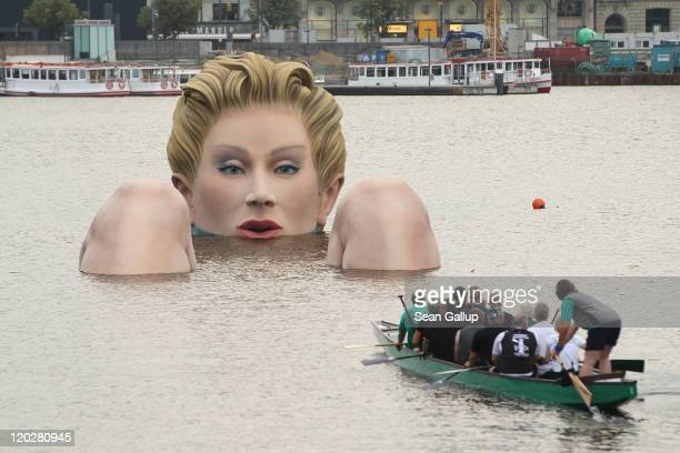 Men in a boat approach Die Badende a giant sculpture showing a woman's head and knees as if she were resting in the Binnenalster lake on August 3...