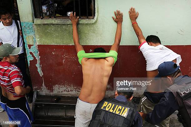 Men in a neighborhood with heavy gang violence are briefly searched by police on July 20 2012 in Tegucigalpa Honduras Honduras now has the highest...