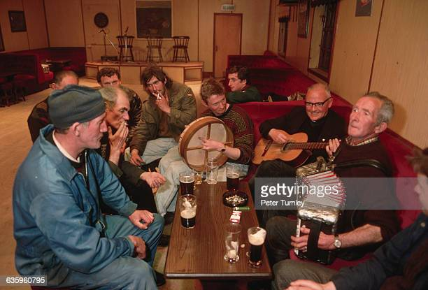 Men in a social club on Tory Island including the island's only priest relax and make music together