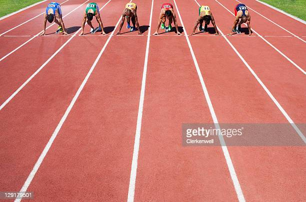 Men in a start block on an athletic track