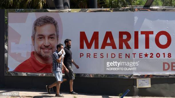 Men in Asuncion on December 16 2017 walk by a billboard will electoral propaganda of Mario Abdo Benitez one of the ruling party's candidates for the...