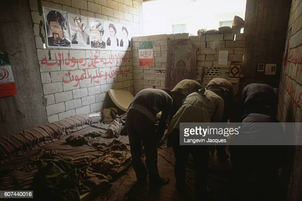 Men in Beirut Lebanon continue with their prayers as peace negotiations take place at the 1984 National Reconciliation Conference in Switzerland In...