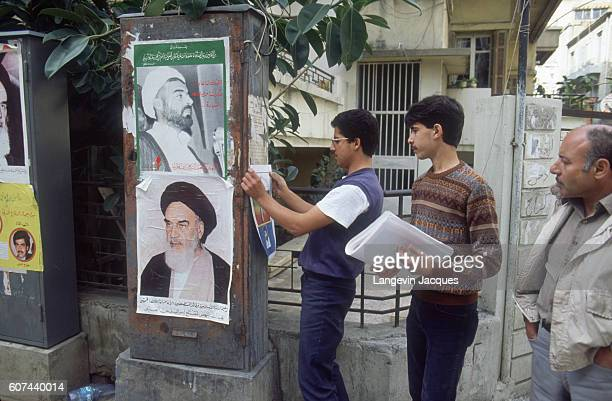 Men in Beirut Lebanon hang posters next to a picture of Ruhollah Khomeini as peace negotiations take place at the 1984 National Reconciliation...