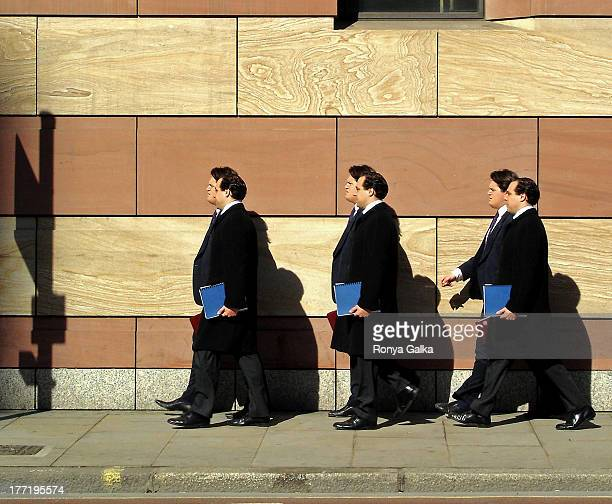 Men in black suits carrying files walking in business district of London