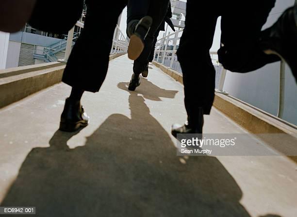 men in black suits running on walkway, low angle view - 追跡 ストックフォトと画像