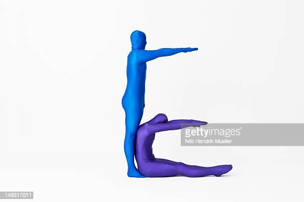 Men in bodysuits making the letter E