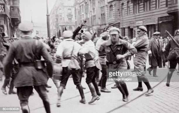 Men in Bolshevik uniform fighting police in the street Germany c1918c1933 From Germany The Olympic Year published by Volk und Reich Verlag Artist...