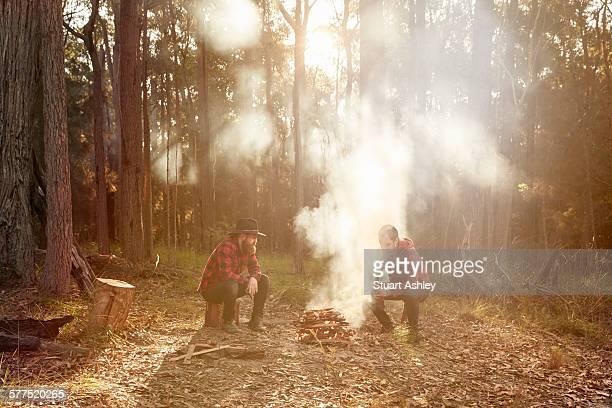 Men in bushland sitting around campfire