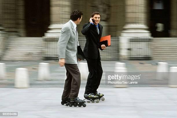 Men in business attire inline skating together along sidewalk, one phoning