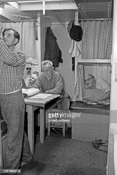 Men in cabin drink coffee and read newspaper Emden Lower Saxony Germany 1950