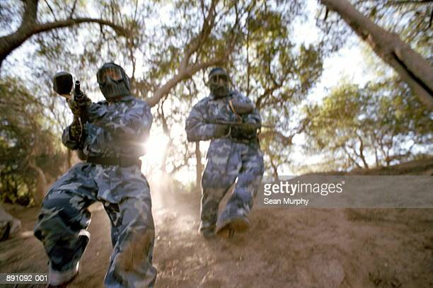 Men in camouflage carrying paint ball guns (blurred motion)