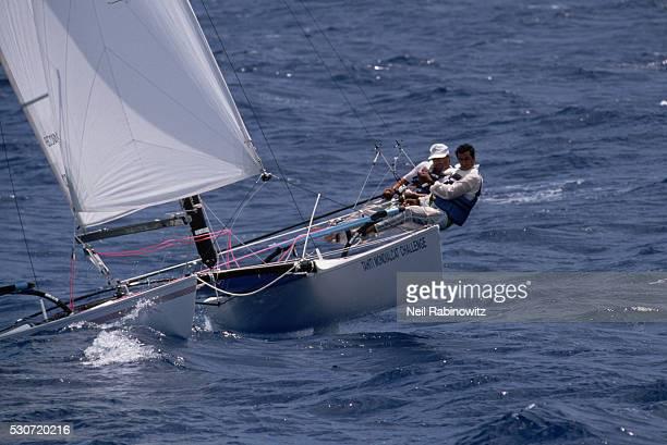 Men in Catamaran Race Lean out of Boat