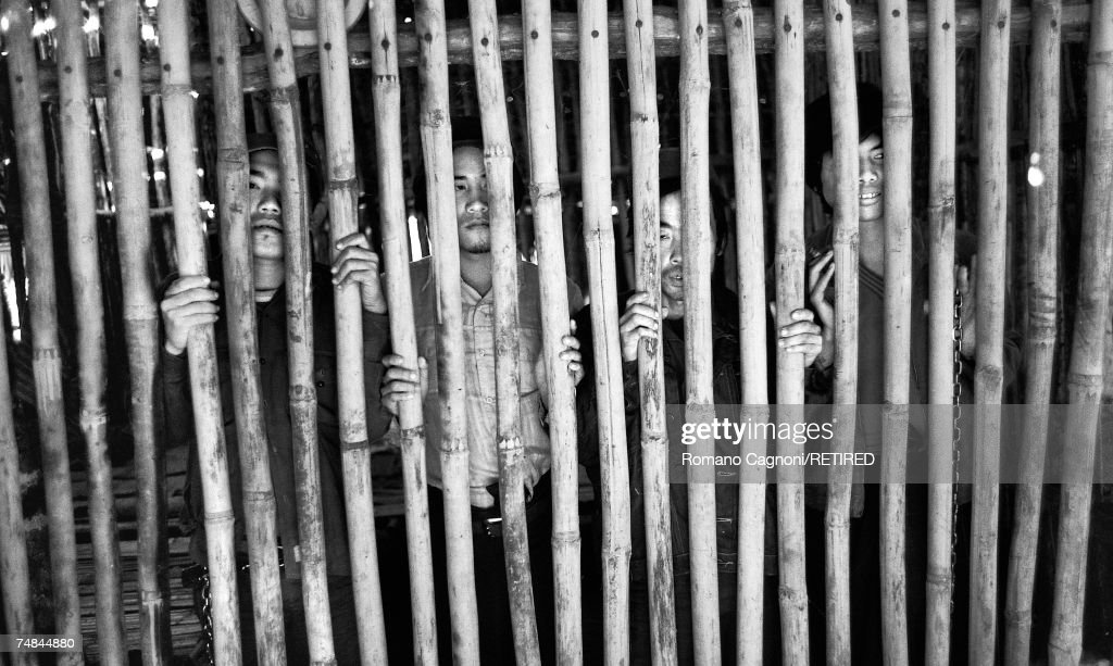 Men in chains behind bamboo bars, Thailand, 1983.