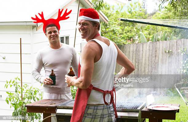 Men in Christmas hats grilling outdoors