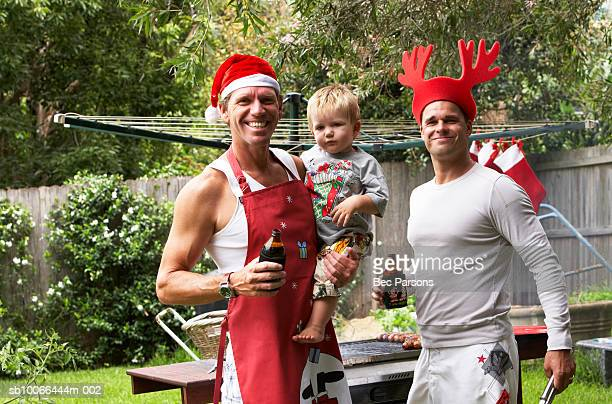 Men in Christmas hats standing by grill, holding son (16-18 months)