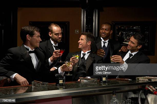 men in dinner jackets drinking cocktails in bar - formal stock pictures, royalty-free photos & images