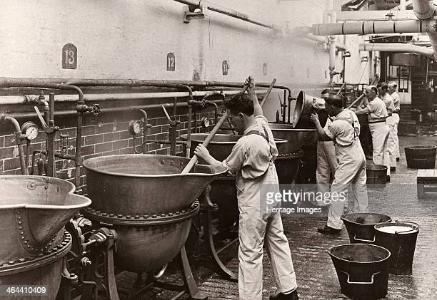 Men in dungarees stir boiling pans in the gum department Rowntree factory York Yorkshire 1925