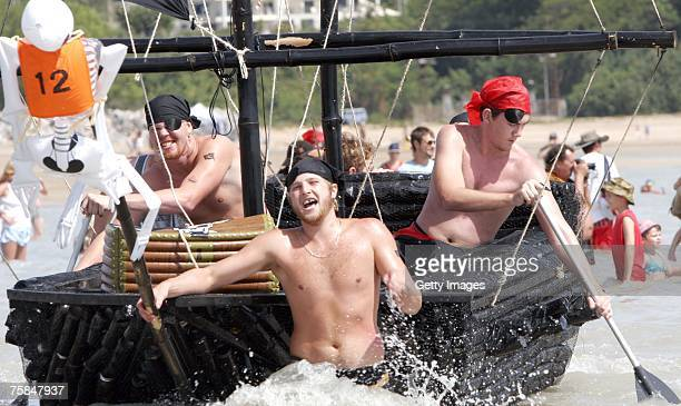 Men in fancy dress row their vessel as thousands flock to Darwin's Mindal beach during the annual Darwin Beer Can Regatta July 29 2007 in Darwin...