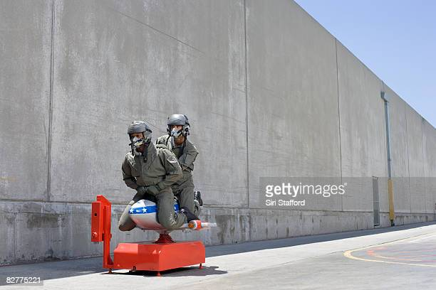 men in fighter pilot suits on toy jet ride - us air force stock pictures, royalty-free photos & images