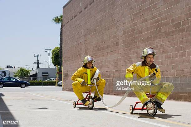 men in firefighter suits on tricycles - fire protection suit stock photos and pictures