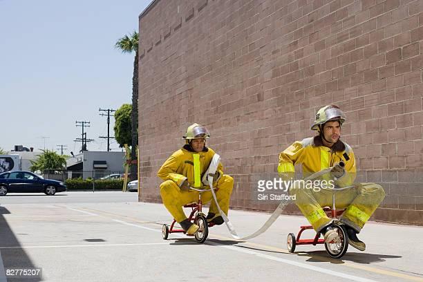 homens em trajes de bombeiro no triciclos - fire protection suit - fotografias e filmes do acervo