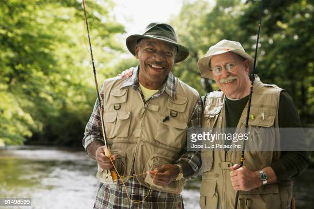 men in fishing vests holding fishing rods - fishing tackle stock pictures, royalty-free photos & images