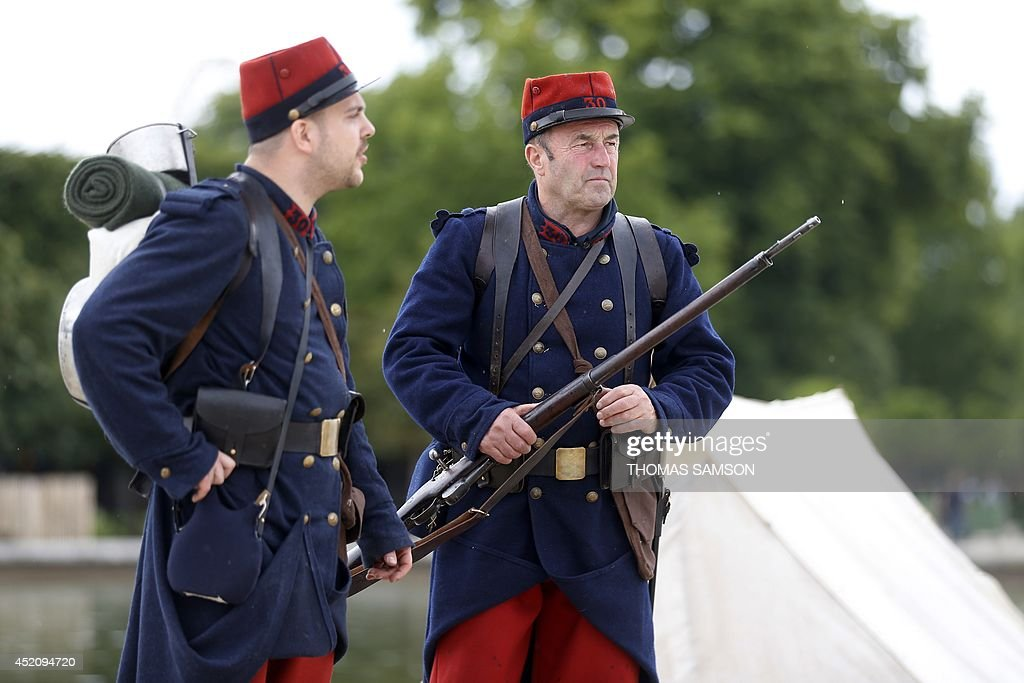 Men in French World War I military uniforms stand on July 13