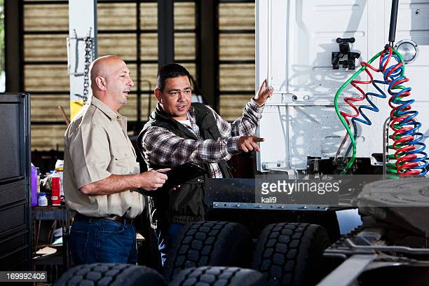 men in garage with semi-truck - trucking stock pictures, royalty-free photos & images
