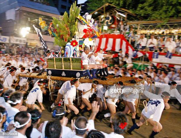 Men in happi coat and loincloth carry a decorated float weighing one ton through Fukuoka city western Japan during the fivekilometer float race...