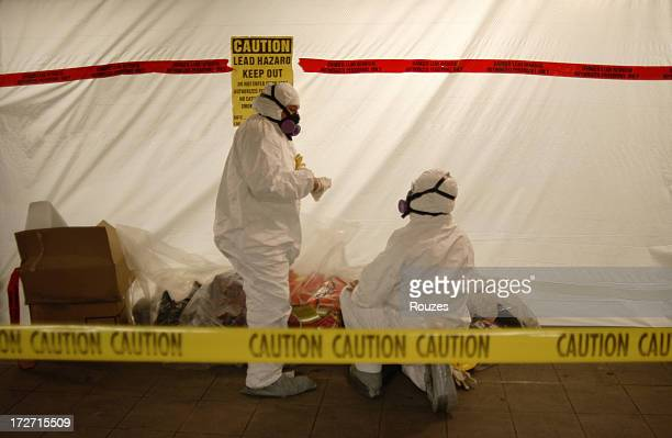 Men in Hazmat suits preparing themselves to work with lead