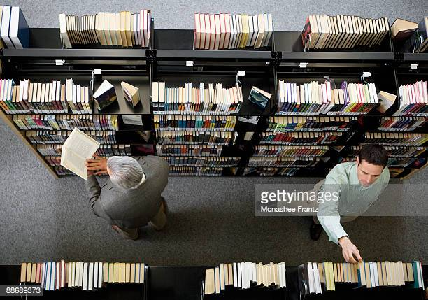 Men in library looking for books