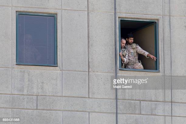 Men in military uniform stand at a window in the Iranian parliament building following an attack on June 7 2017 in Tehran Iran At least 12 people...