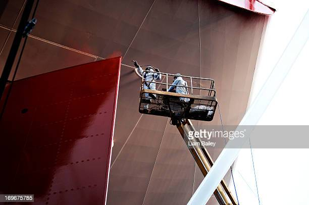 Men in overalls painting  large ship in dry dock