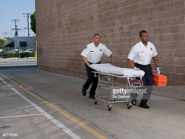 Hommes en Auxiliaire médical uniformes pousser gurney
