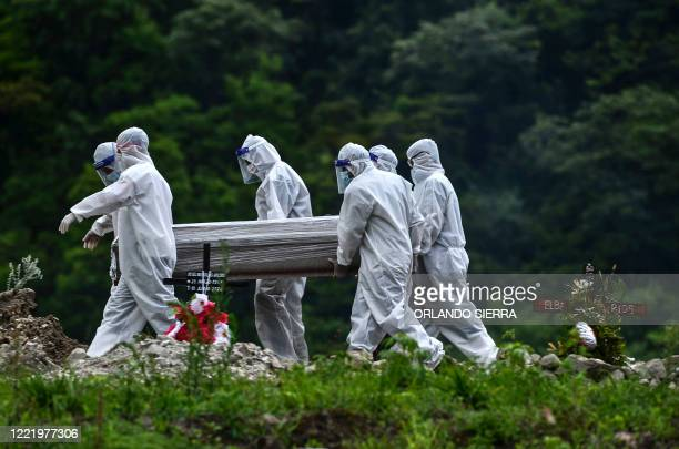 Men in protective suits carry the coffin of an alleged victim of the new coronavirus at the Parque Memorial Jardin de los Angeles cemetery 14 km...