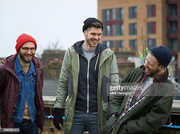 Men in roof garden wearing coats laughing.