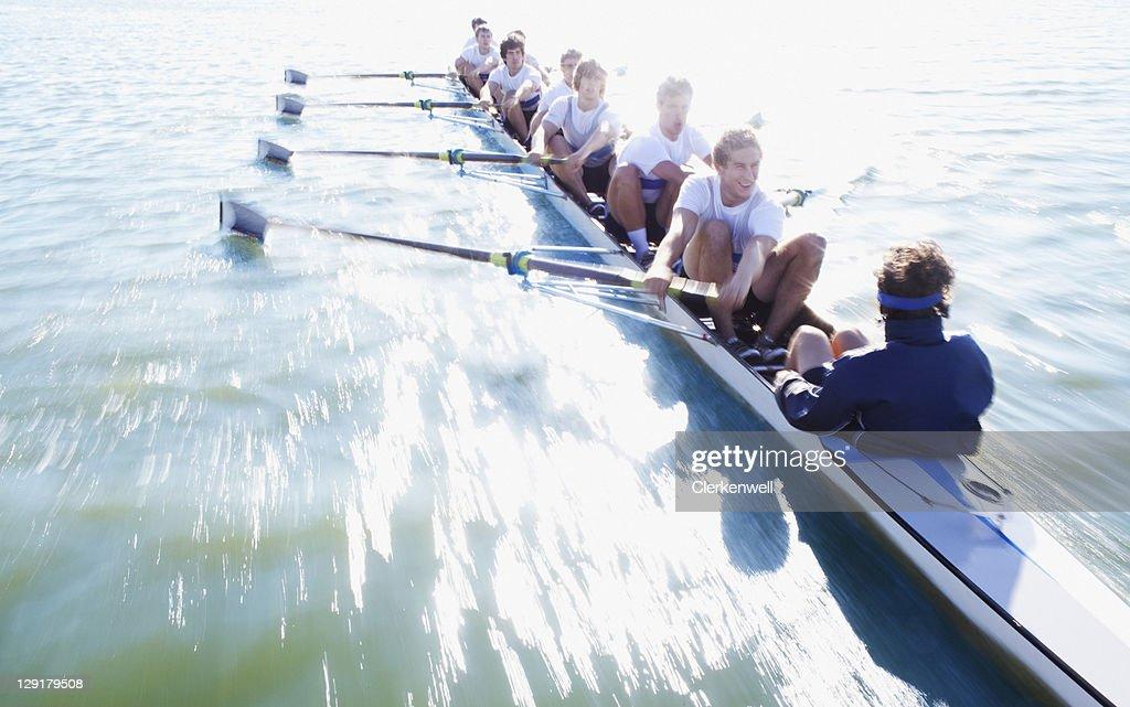 Men in row boat oaring : Stock Photo