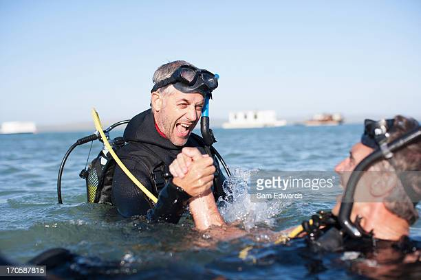 Men in scuba gear holding hands