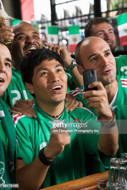 Men in sports bar using camera phone