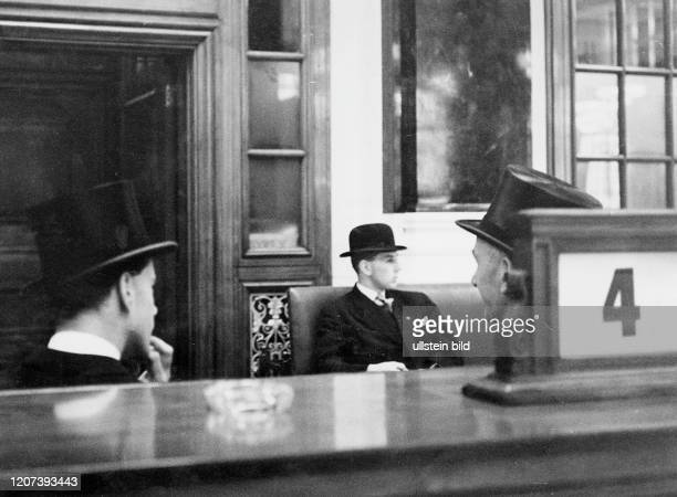 Men in suits with Bowler hats and top hats sitting in the Stock Exchange of London Published in: Berliner Zeitung
