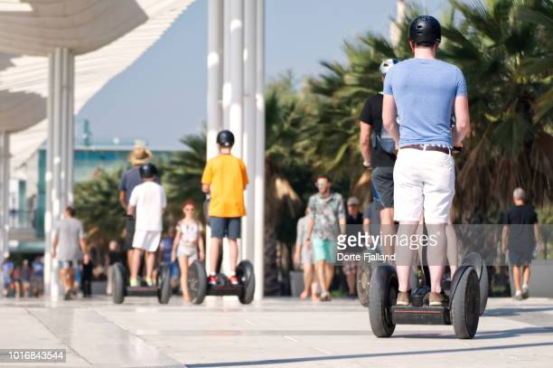 Men in Summer clothes and helmets on segway on a sunny day
