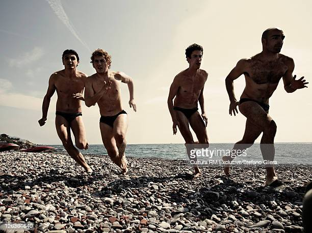 Men in swimsuits running on rocky beach