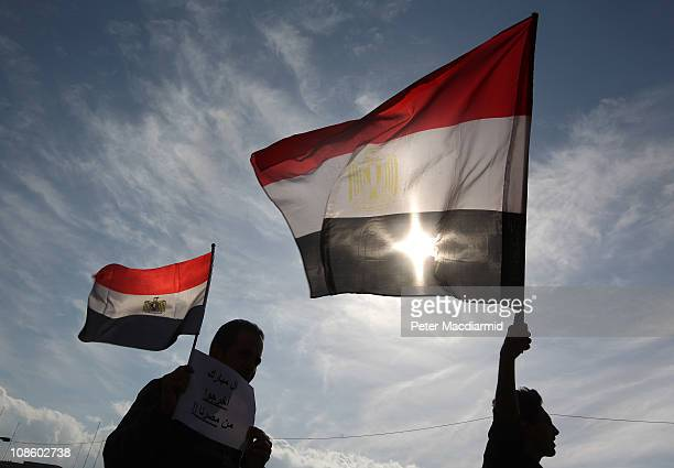 Men in Tahrir Square hold Egyptian flags on January 30, 2011 in Cairo, Egypt. As President Mubarak struggles to regain control after five days of...