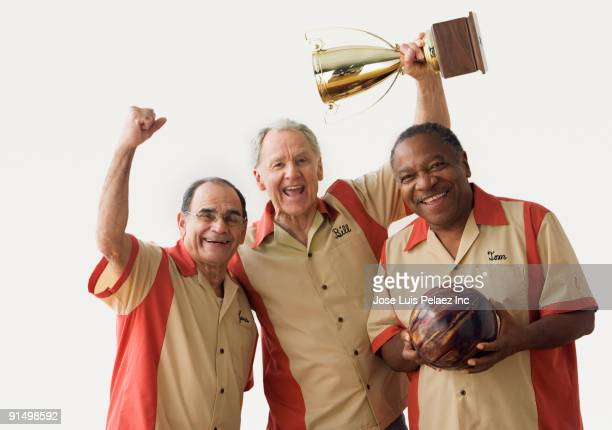 men in team uniforms holding bowling ball and trophy - only senior men stock pictures, royalty-free photos & images