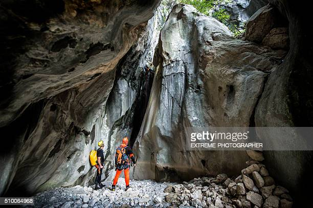 Men in the cave looking at huge rock cliff