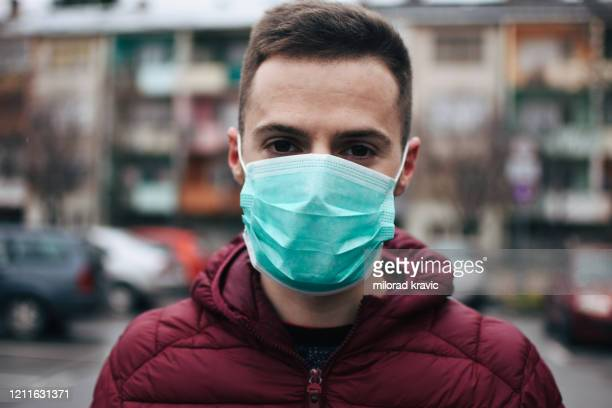 men in town wearing protective face mask - face masks imagens e fotografias de stock
