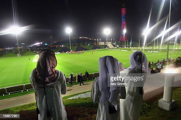 Men in traditional clothes view a Bayern Muenchen training session at the ASPIRE Academy for Sports Excellence on January 2 2013 in Doha Qatar