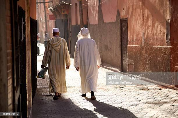 Men in traditional clothing walking in Medina.
